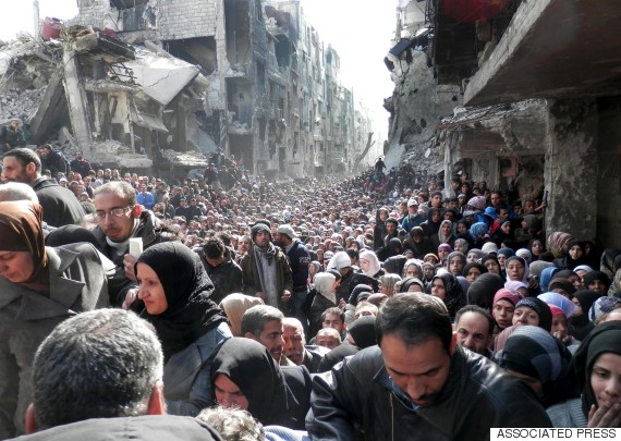 In this Jan. 31, 2014, file photo released by theUnited Nations Relief and Works Agency for Palestine Refugees in the Near East (UNRWA),residents of the besieged Yarmouk refugee camp near Damascus, Syria, queue to receive food supplies. Conditions in the camp have deteriorated since Islamic State militants muscled their way into it in early April 2015. The militants are trying to consolidate their hold on the camp. (AP Photo/UNRWA, File)