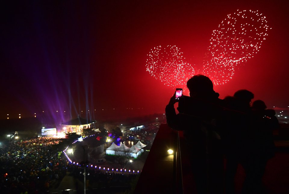 South Koreans take pictures of fireworks during a countdown event to celebrate the New Year at Imjingak peace park in the border city of Paju near the demilitarized zone dividing the two Koreas on December 31, 2015. AFP PHOTO / JUNG YEON-JE / AFP / JUNG YEON-JE (Photo credit should read JUNG YEON-JE/AFP/Getty Images)