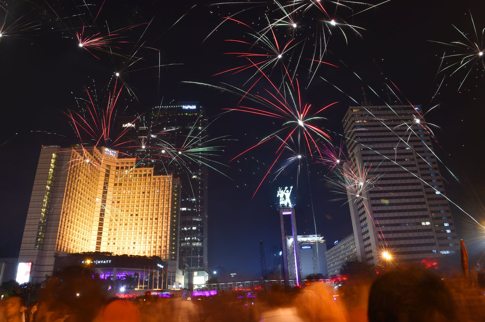 Indonesians gather and take a look of fireworks during a countdown event to celebrate the New Year in Jakarta on December 31, 2015. AFP PHOTO / Bay ISMOYO / AFP / BAY ISMOYO (Photo credit should read BAY ISMOYO/AFP/Getty Images)
